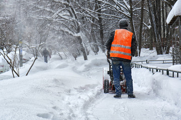 Janitor removing snow from the moscow street using snow blower
