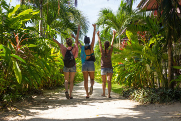 Three girls in shorts walking towards the beach with their hands in the air through a sand path surrounded by nature in the island of Koh Phangan, Thailand. Happy young lady friends enjoying vacation