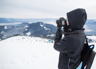 photographer in the winter, on top of the mountain