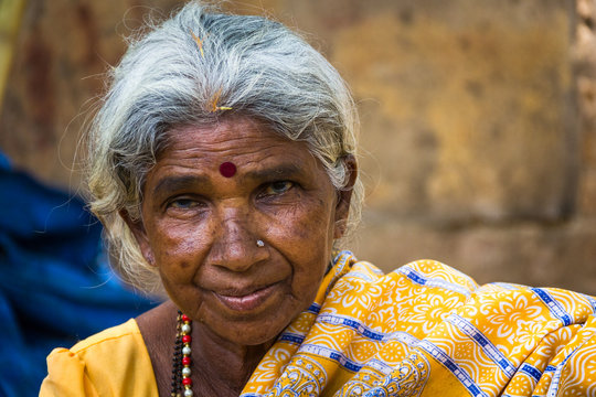 Portrait of Indian elder lady with traditional bindi as a third eye, piercing on nose and wearing a yellow saree in Mysore, Karnataka, India. Close up on Indian ethnicity old woman
