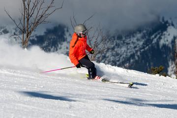 Junge Frau auf einer Skipiste bei der Abfahrt ins Tal