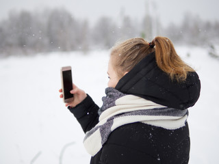 girl photographs a winter forest to your smartphone during a snowfall