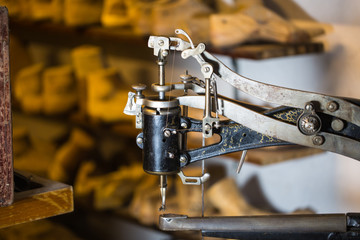 Sewing machine in a shoe workshop, shoe lasts in the background