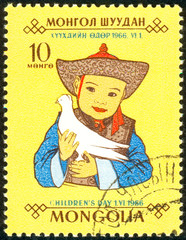 Ukraine - circa 2018: A postage stamp printed in Mongolia show the Mongolian child in a bright national costume holds a white dove in his hands. Series: Day of the child. Circa 1966.