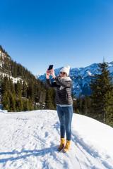 Junge attraktive Frau macht Fotos mit Smartphone im Schnee