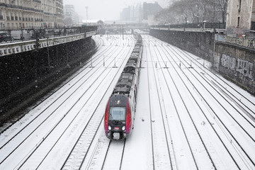 A train of French state-owned railway company SNCF and railroad tracks are seen under the falling snow at Pont-Cardinet railway station in Paris