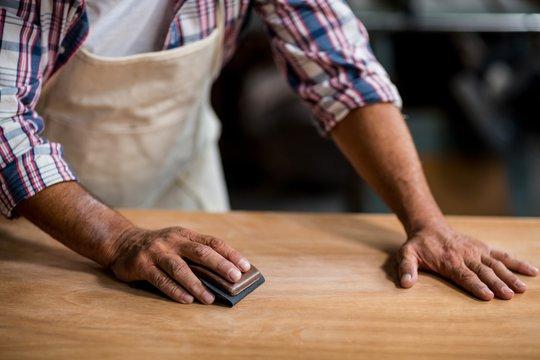 Carpenter rubbing wood with sanding block