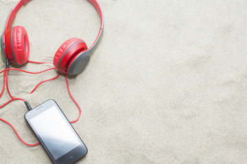 phone with headphones on sand in a summer beach.