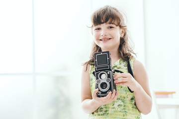 Young girl holding a vintage camera