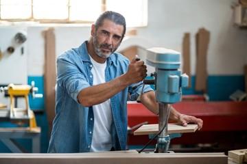 Carpenter using machinery in workshop
