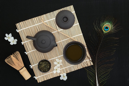 Japanese sencha sukiygu makoto tea ceremony with equipment including oriental teapot, cups, whisk, scoop, tea leaves, spring cherry blossom and peacock feather on bamboo and black ridged background.