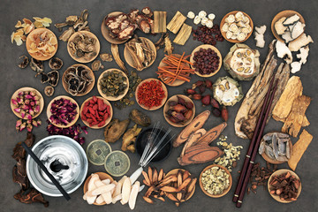 Chinese alternative medicine with herbs, acupuncture needles, moxa sticks used in moxibustion therapy and feng shui coins. Top view.