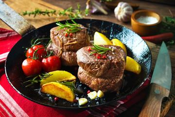 Juicy medium beef fillet steaks mignon in pan on table