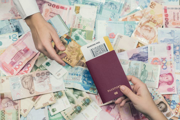 Foreign passport with boarding pass.  Money of south-east Asia and American hundred dollar bill. Currency of Hong Kong, Indonesia, Malaysia, Thai, Singapore dollar. Travel concept