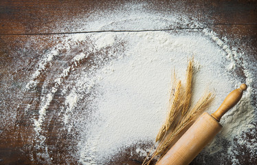 Baking background with the rolling pin, wheat and flour on the wooden table