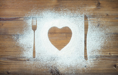 Fork, knife and plate in heart shape, flour sprinkled around cutting board