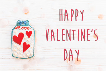 happy valentine's day text sign flat lay. cookie hearts in jar and confetti on white rustic wooden background. space for text. greeting card concept. valentines bright image