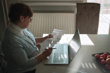 Mature woman going through home budget and reading bills.