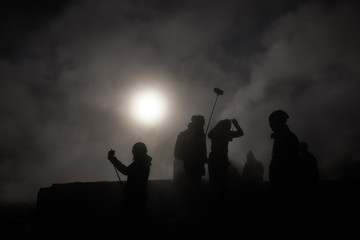 Silhouettes of a Camera Crew at a Smoky Geyser