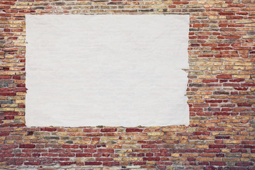 blank advertising poster glued to the brick wall