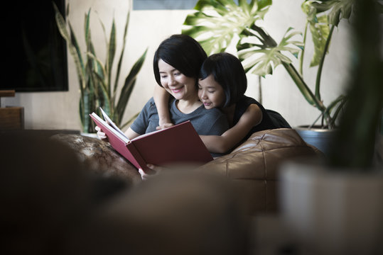 Young happy Asian mother and daughter reading a book at home.