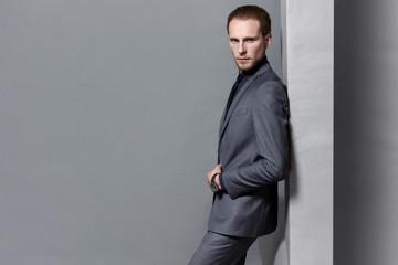 man bearded in gray suit posing standing gray studio background
