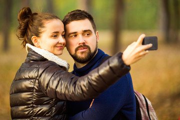 couple in love in autumn makes selfie