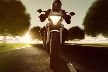 Motorrad fährt auf Allee