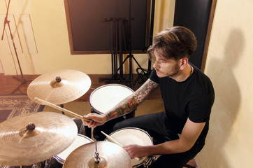 Handsome young man playing drums in studio