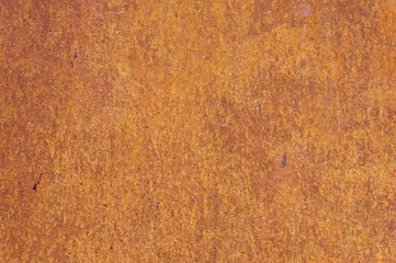 Rusty yellow-red textured metal surface. The texture of the metal sheet is prone to oxidation and corrosion. Grunge background