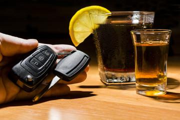 A man's hand holding car keys at a bar