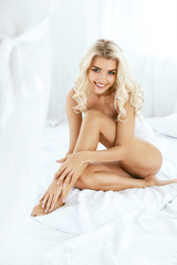 Smiling Woman With Fit Body And Beautiful Legs On White Bed