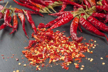 Dried red chile pepper with ground on a dark background