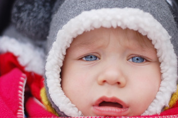 A sad little boy with blue eyes sitting in a baby carriage on the street. He is dressed in warm winter clothes