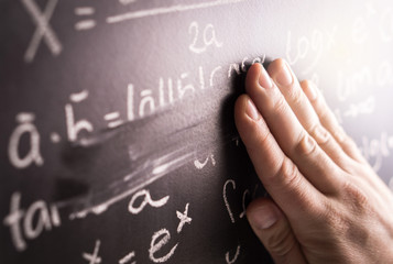 Making mistakes and wrong answer concept. Hand wiping math formula off blackboard in classroom at...