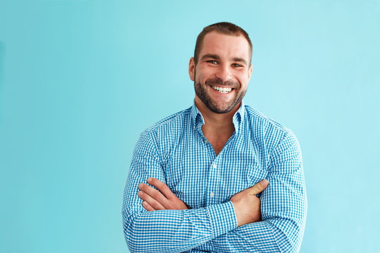 Happy man standing in front of turquoise wall