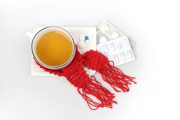 Eine Tasse mit Tee umwickelt von einem roten Schal und Tabletten nebenliegend
