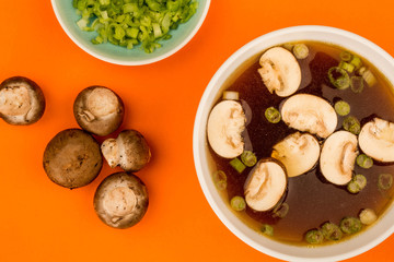 Bowl Of Japanese Style Clear Onion Soup With Mushrooms and Spring Onions