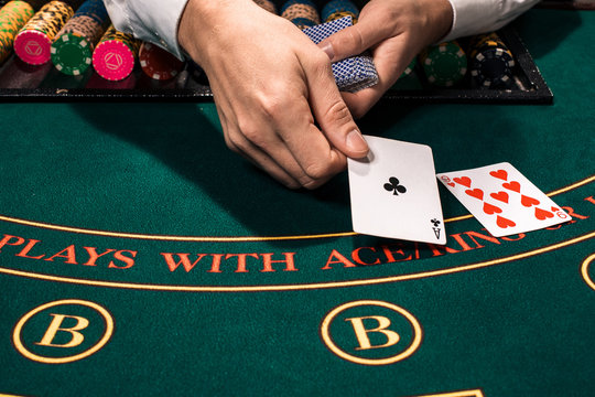 Close up of holdem dealer with playing cards and chips on green table