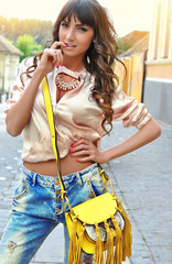 Beautiful young brunette caucasian woman wearing a beige bomber jacket blue jeans yellow purse with tassel. Sexy look