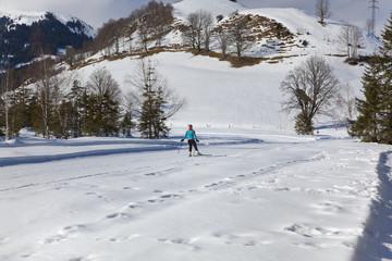 Winterpanorama im Salzburger Land in den Kitzbühler Alpen (Mooralm) mit Langlaufloipe und Langläuferin