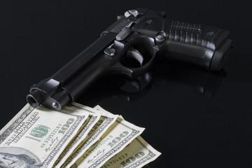 Silah ve para siyah zemin üstünde