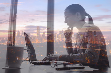 Woman working on her office computer in the city. Double exposure.