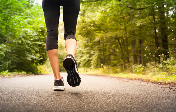 Woman taking a walking running on a country road.  People fitness nature concept.