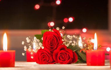 Wall Mural - Beautiful red roses net to candle lights.