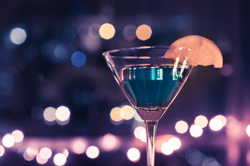Martini drink against colorful lights.