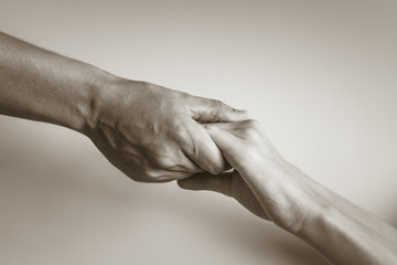 Hand holding up hand. Giving blessing and help.
