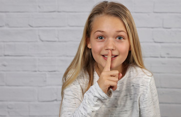 Portrait of happy smiling 10 years old kid girl showing silence gesture