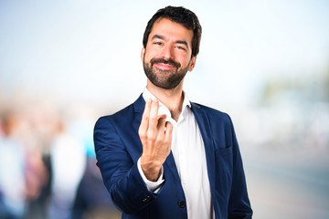 Handsome man coming gesture on unfocused background