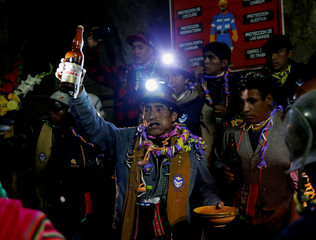 An independent miner toasts during a ceremony to bless the mine by offering animal sacrifice as part of Andean carnival celebrations, outside the Mina Itos on the outskirts of Oruro